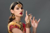 elegant indian woman gesturing in sari and accessories, isolated on grey