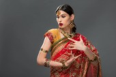 attractive indian woman gesturing in sari and accessories, isolated on grey