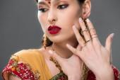 elegante Indianerin in Sari und Accessoires, isoliert auf grau