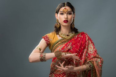 attractive indian woman gesturing in traditional clothing, isolated on grey