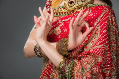 cropped view of indian woman in traditional clothing showing gyan mudra, isolated on grey