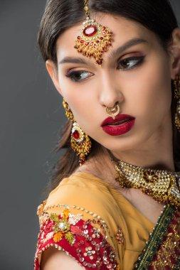 beautiful indian woman posing in traditional sari and bindi, isolated on grey