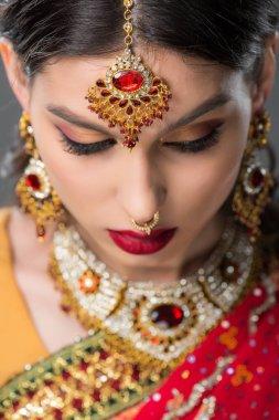 beautiful indian girl posing in traditional bindi, isolated on grey