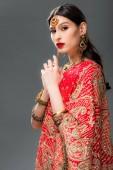 attraktive Inderin in Sari und Bindi, isoliert auf grau