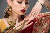 schöne Indianerin im Sari und Accessoires an den Händen, isoliert auf grau