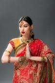 Fotografie schöne Indianerin in traditioneller Kleidung mit namaste mudra, isoliert auf grau