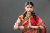 Indianerin in traditioneller Kleidung und Accessoires mit namaste mudra, isoliert auf grau
