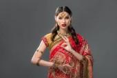 Fotografie attraktive Inderin in Sari und Zubehör mit Gyan Mudra, isoliert auf grau