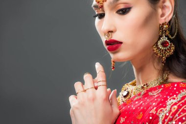 beautiful indian woman in sari and accessories, isolated on grey
