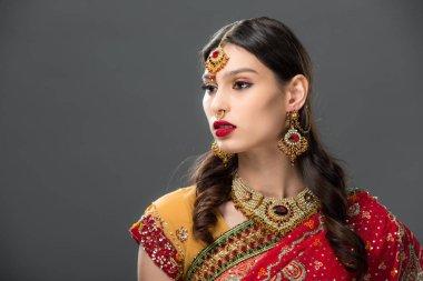 attractive indian woman in sari and bindi on head, isolated on grey