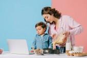 Mutter gießt Teig in Backform, während kleiner Sohn auf Laptop-Display auf zweifarbigem Hintergrund blickt