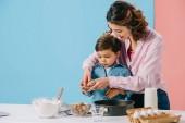 Krásná matka s roztomilý malý syn popraskání vlašské ořechy při vaření společně na bicolor pozadí