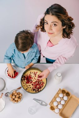 top view of mother and son adding cranberries to dough in baking form on light background