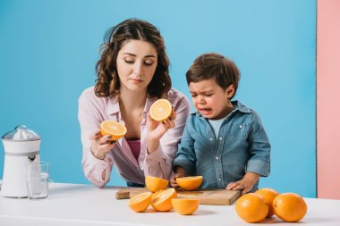 mother holding cut oranges and little son crying while standing at kitchen table on bicolor background