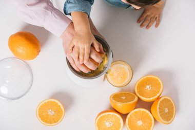 cropped view of mother and child squeezing fresh orange juice together on white background