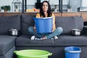 Fáradt nő ül a kanapé, nagy kék vödör