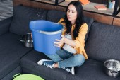 Wonderful young woman sitting on sofa with blue bucket