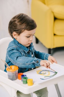 Adorable little boy painting with watercolor paints while sitting on highchair stock vector