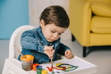 Cute little boy painting with watercolor paints while sitting on highchair stock vector