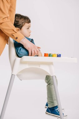 mother hugging little son sitting on highchair with watercolors set on table isolated on white