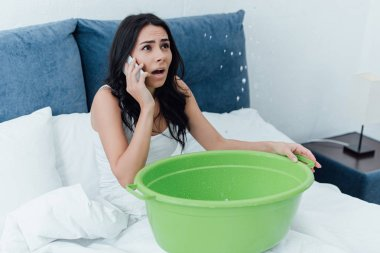 Frightened woman talking on smartphone and looking at water leak in bedroom