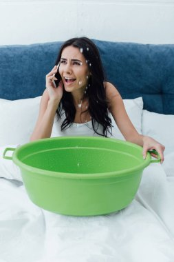 Worried girl talking on smartphone and holding basin in bed