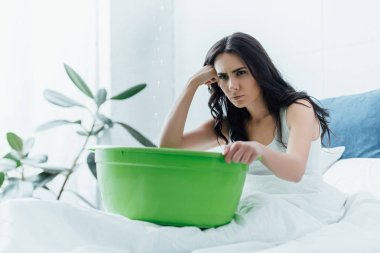 Sad woman sitting in bed with basin during water leak