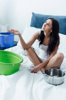 Sad young woman sitting on bed with bucket and pots during water leak