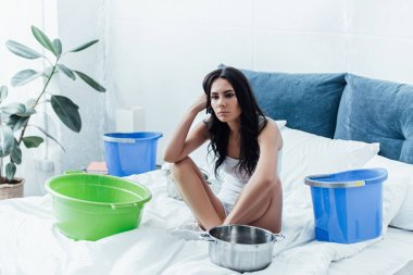 Pensive young woman dealing with water leak in bedroom