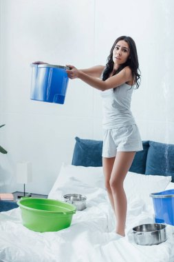 Frightened woman standing on bed with buckets and pots