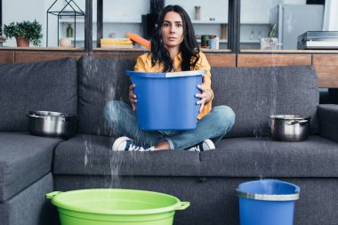 Brunette woman holding bucket on sofa during water damage in living room