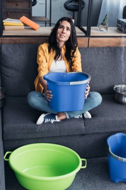 Upset woman with buckets and basin looking at leaking ceiling