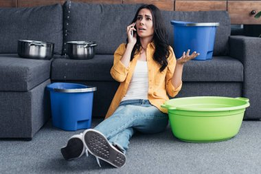 Worried woman talking on smartphone and sitting on floor under leaking ceiling in living room