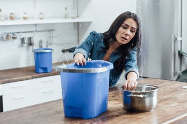 Stressed young woman using buckets and pot during leak in kitchen