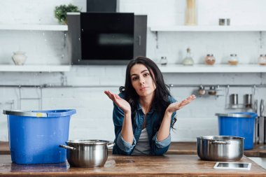 Brunette woman using pots and buckets during leak in kitchen