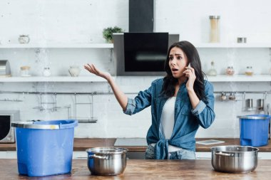 Worried woman looking at water leaking from ceiling and calling plumber