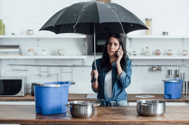 Upset woman standing under umbrella in kitchen and calling plumber