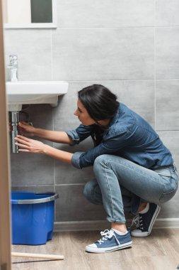 Brunette woman in jeans fixing pipe in bathroom