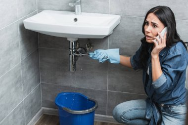 Shocked woman talking on smartphone while repairing pipe in bathroom