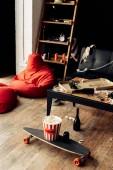 gördeszka popcorn doboz közelében rendetlen nappaliban a dohányzóasztal
