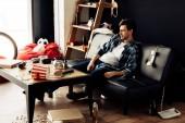 Fényképek részeg ember ül a rendetlen nappaliban kanapé buli után