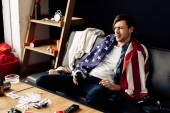 sleepy man holding can with beer and sitting with american flag on sofa