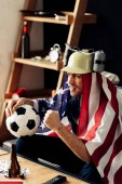 man wearing beer helmet watching game with american flag on shoulders