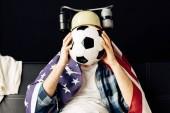 muž nosí pivo helma pokrývající obličej s fotbalovými a sedí s americkou vlajkou na bedrech