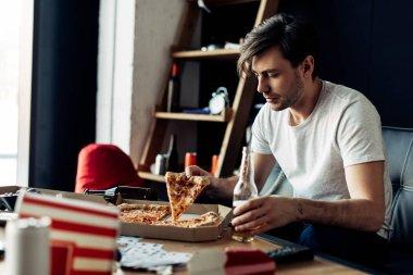 """Картина, постер, плакат, фотообои """"пьяный человек, держащий ломтик вкусную пиццу и бутылка в гостиной"""", артикул 243423812"""