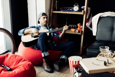 man in cap playing acoustic guitar at messy living room