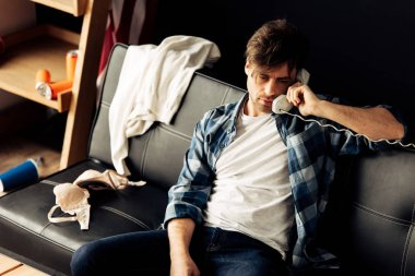 drunk man talking on retro phone and sitting on sofa after party at home