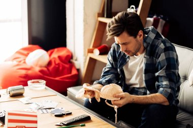 confused man looking at bra while sitting on sofa after party