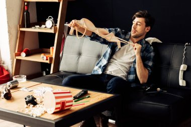 man holding bra while sitting on sofa after party