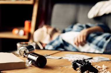 selective focus of bottle lying on coffee table with man sleeping with bra on face on background